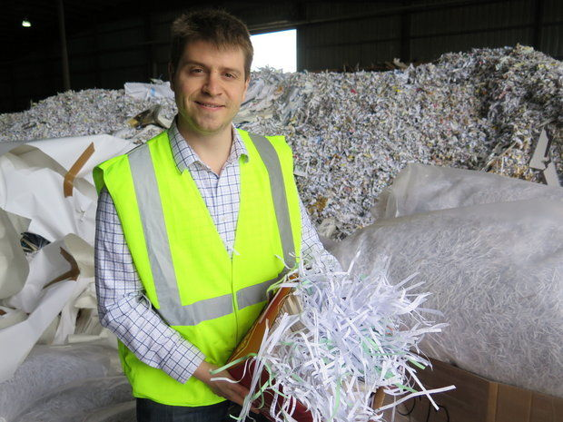 Aaron Goodman, chief operations officer at Northstar Pulp & Paper in Springfield, shows a sample of paper that the company will accept in its new cash-for-paper program targeting the general public. (Judith Kelliher)